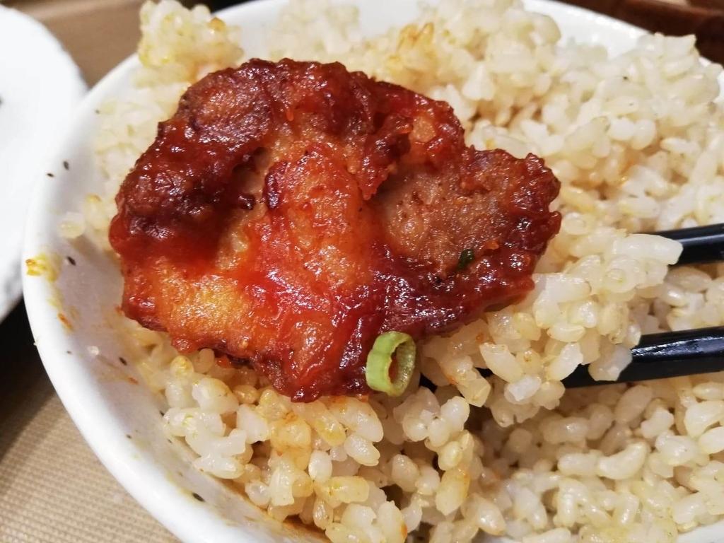箸で掴んだ、秋葉原『おむすびのGABA』のマウンテンヤンニョムチキン定食の唐揚げと発芽玄米