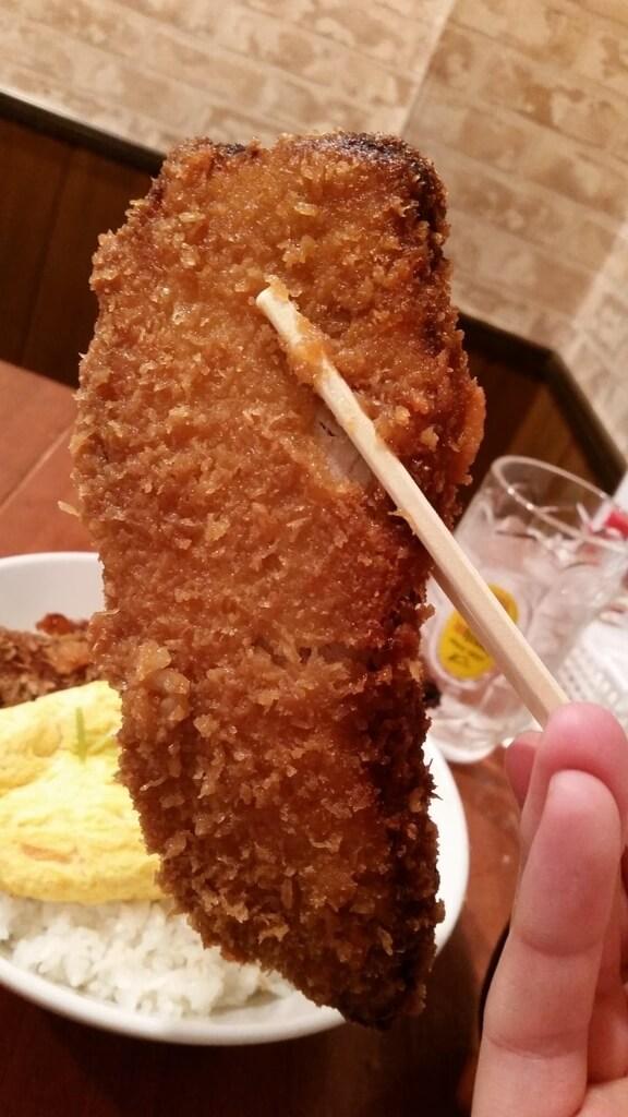 箸で掴んだ、炉端バルさま田のとろとろ玉子の角煮かつ丼ダブル大盛りの角煮かつ