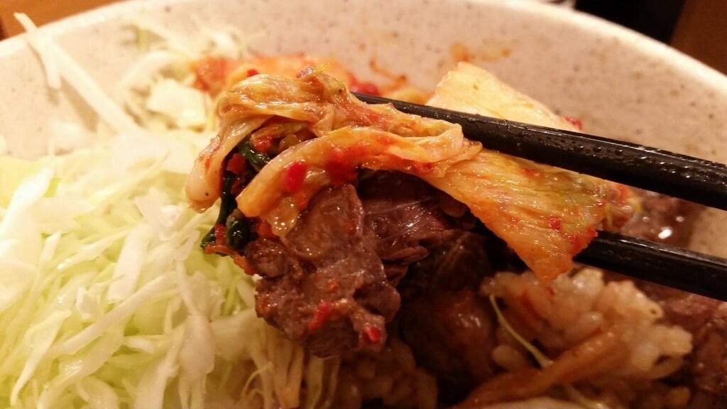 箸で掴んだ、丼やまののハラミ丼肉トリプルご飯大盛りのハラミ肉とキムチ