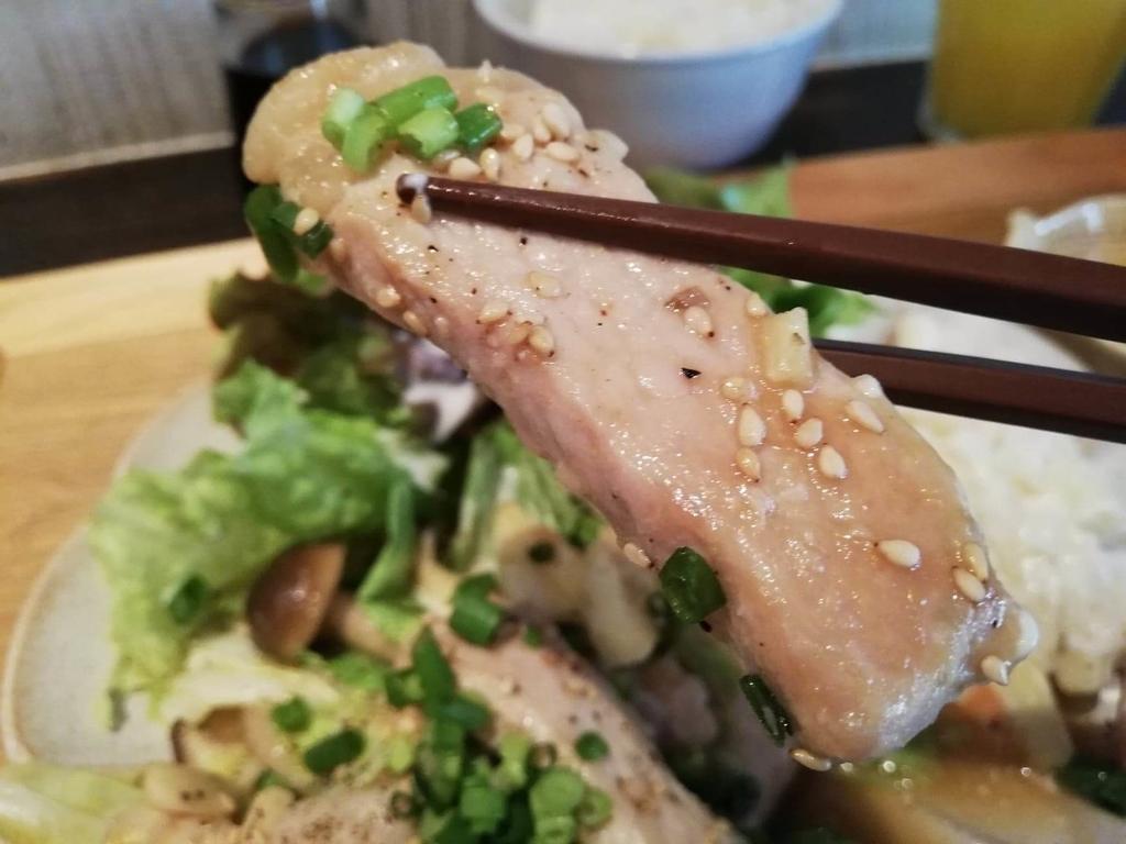箸で掴んだ北千住『あさり食堂』の、豚肉としめじの味噌バター炒め定食の豚肉