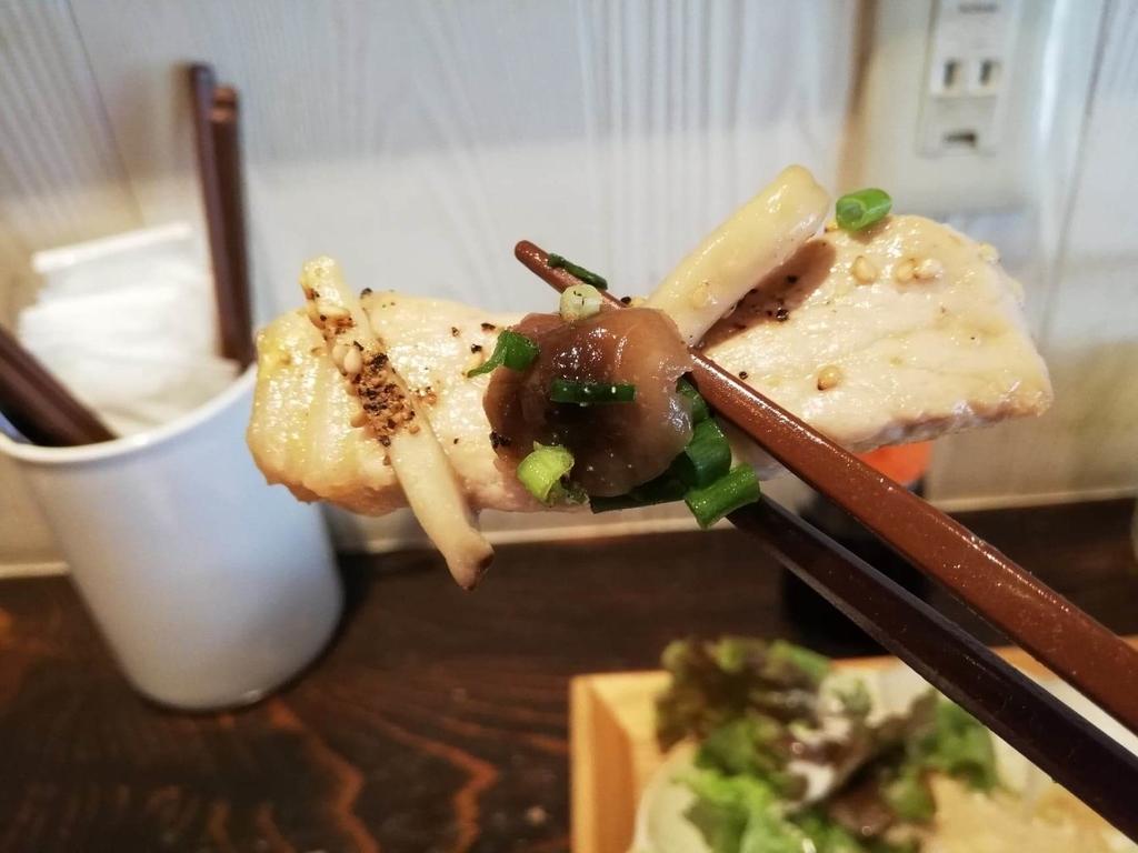 箸で掴んだ北千住『あさり食堂』の、豚肉としめじの味噌バター炒め定食のしめじと豚肉