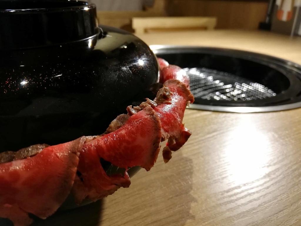 浅草焼肉たん鬼『鬼く丼』のお椀からお肉がはみ出ている写真