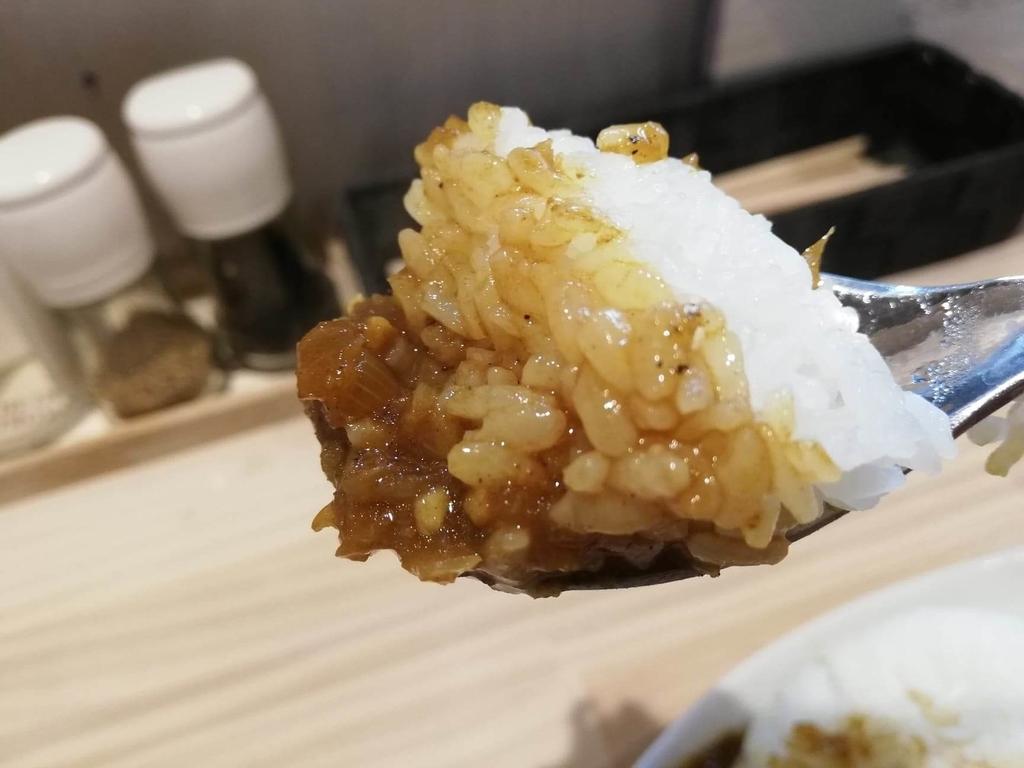 渋谷『吉法師』の『鶏清湯 青』のセットミニカレーをスプーンですくっている写真