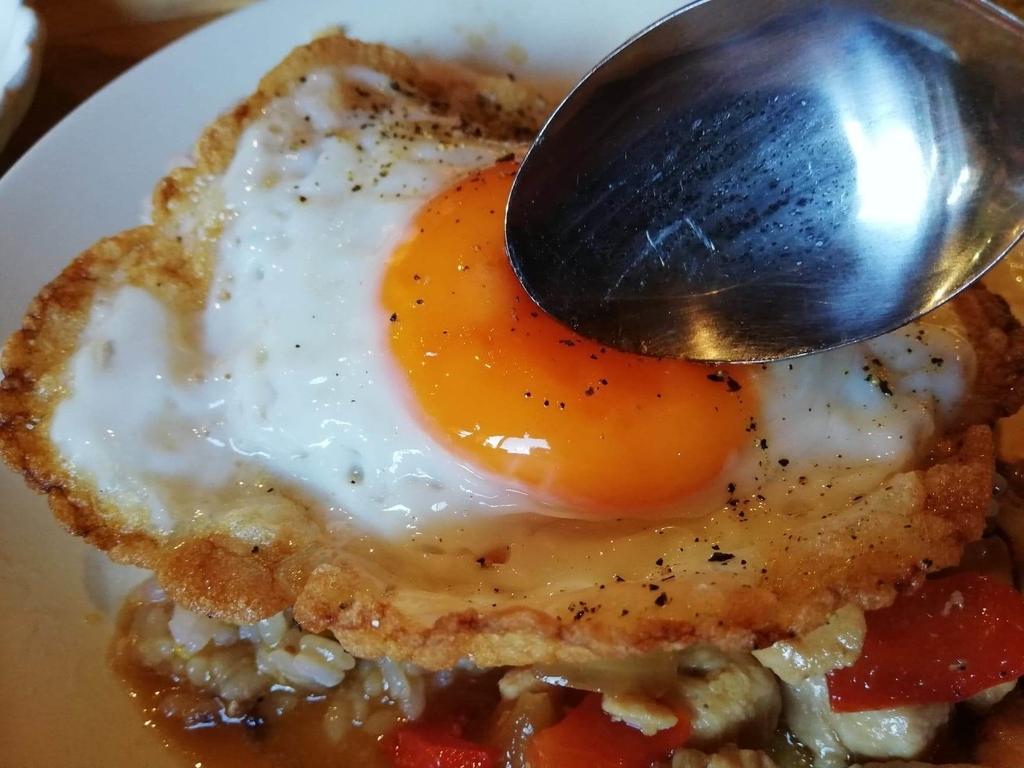 北千住のカフェ『寛美堂』のガパオライス定食に乗っている目玉焼きをスプーンで潰している写真