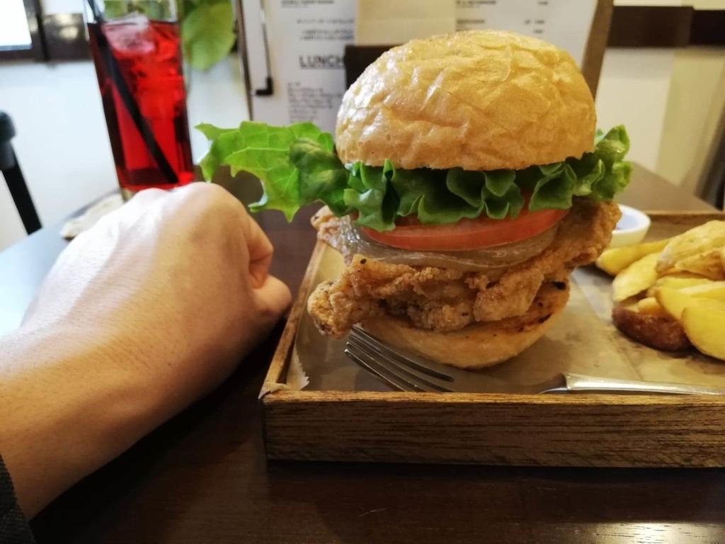 上野(御徒町)『ゴールデンゲート(GOLDEN GATE)』のフライドチキンバーガーと拳のサイズ比較写真