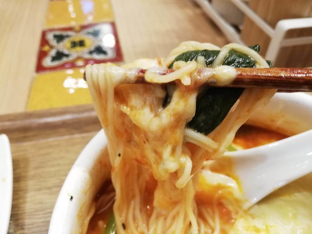 新宿ミロード店『太陽のトマト麺withチーズ』の、太陽のチーズラーメンの麺とほうれん草を箸で持ち上げた写真