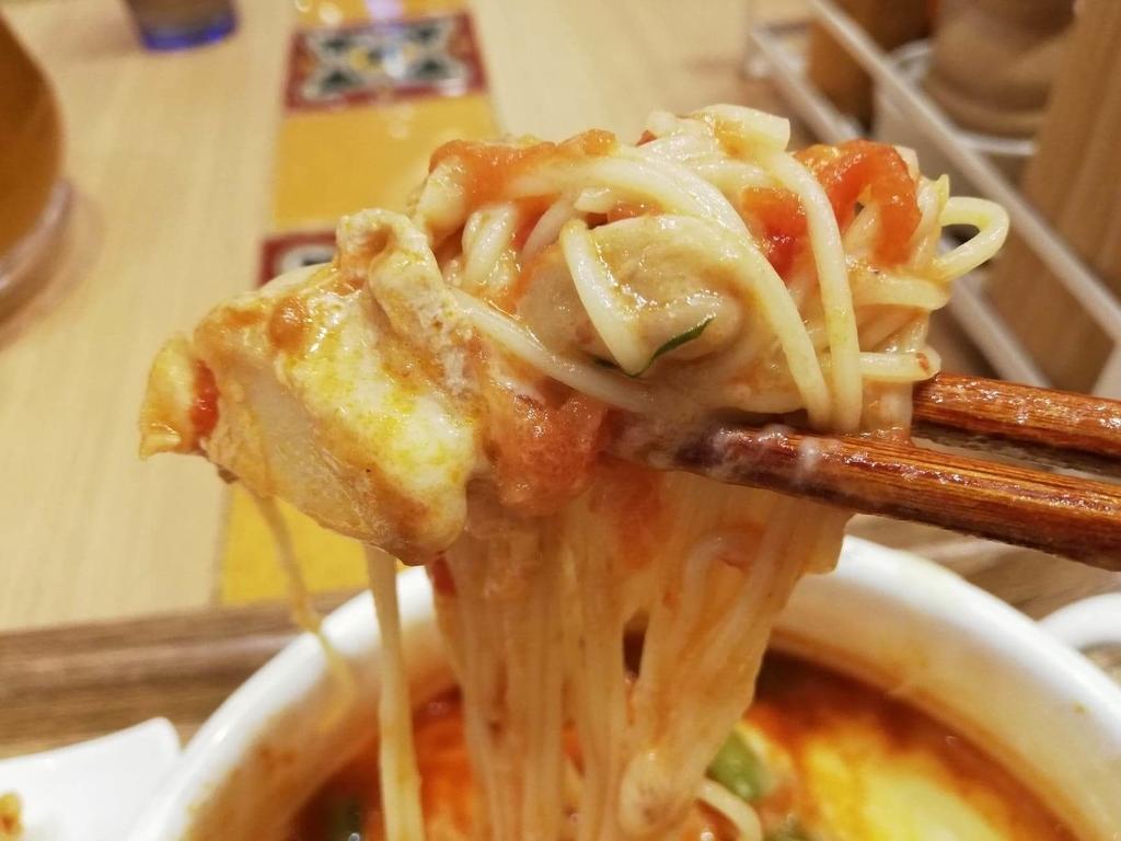 新宿ミロード店『太陽のトマト麺withチーズ』の、太陽のチーズラーメンの麺とチキンを箸で掴んだ写真