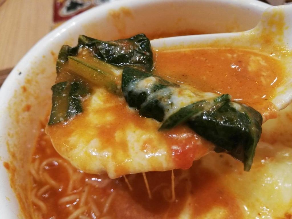 新宿ミロード店『太陽のトマト麺withチーズ』の、太陽のチーズラーメンのスープとほうれん草をレンゲで持ち上げた写真