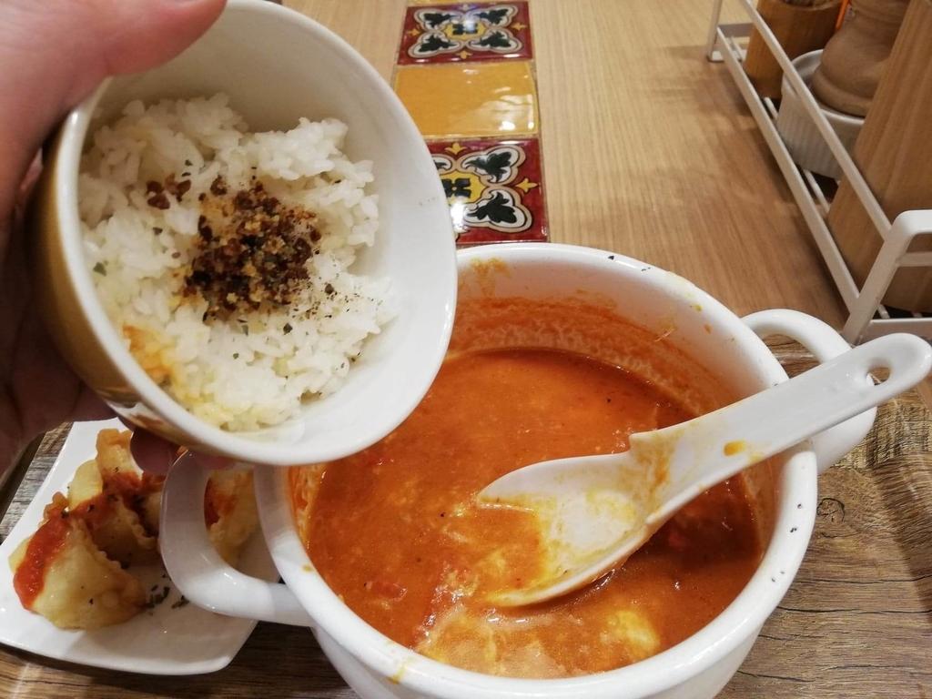 新宿ミロード店『太陽のトマト麺withチーズ』の、太陽のチーズラーメンにライスを入れている写真