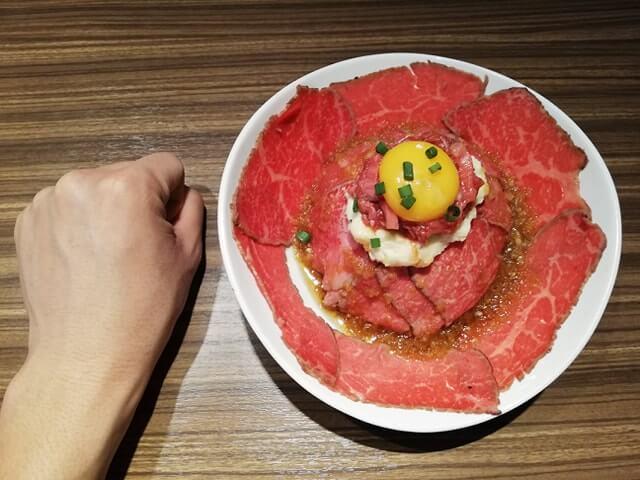 新宿『焼肉ブルズ』の特選和牛のローストビーフ丼と拳のサイズ比較