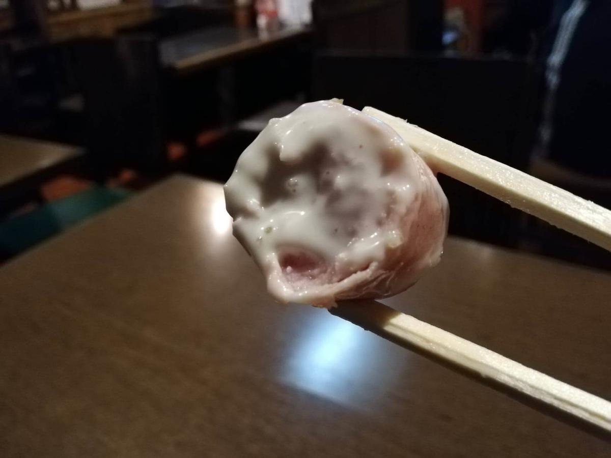 六本木『居酒屋のんでこ』のセクシーチャーハンのソーセージを箸で掴んだ写真