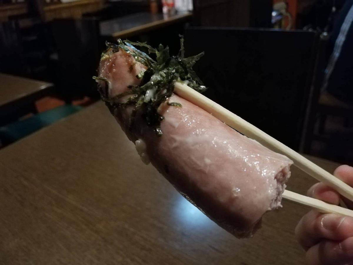 六本木『居酒屋のんでこ』のセクシーチャーハンのソーセージを、海苔と一緒に箸で掴んでいる写真