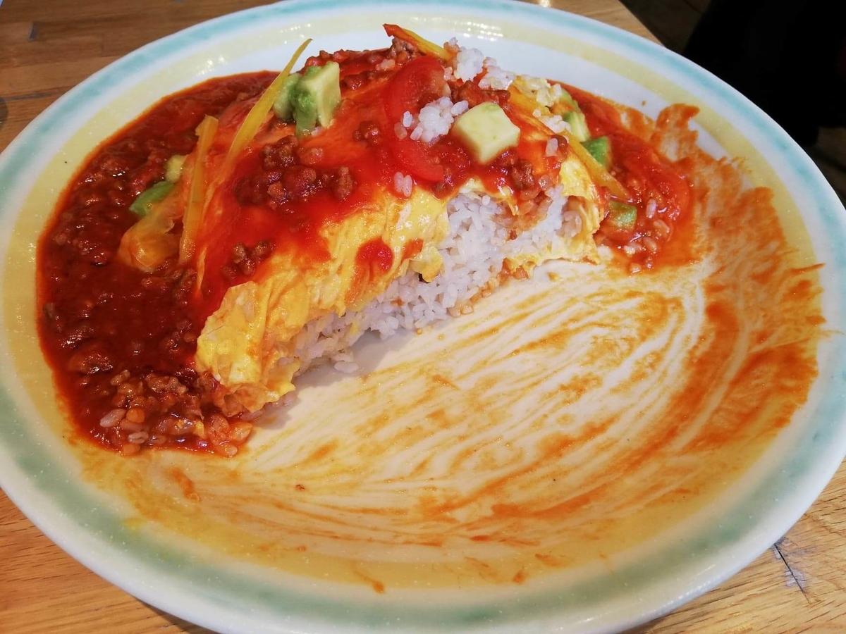 残り半分の、渋谷『ポムの樹』のアボカドとモッツァレラチーズのトマトミンチオムライスの写真