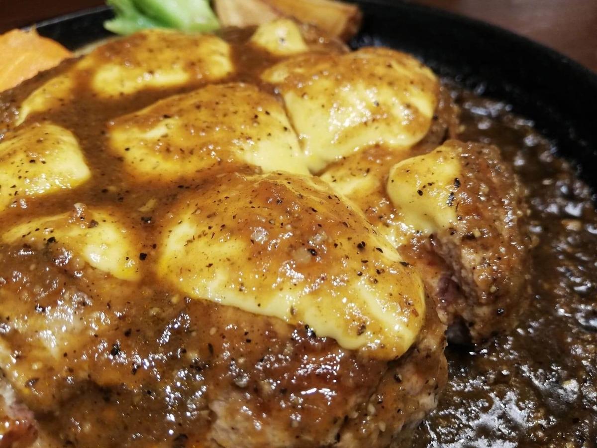 記事トップの、池袋『札幌牛亭』の、平日ランチタイム限定ハンバーグステーキセットのハンバーグに乗っているチェダーチーズのアップ写真