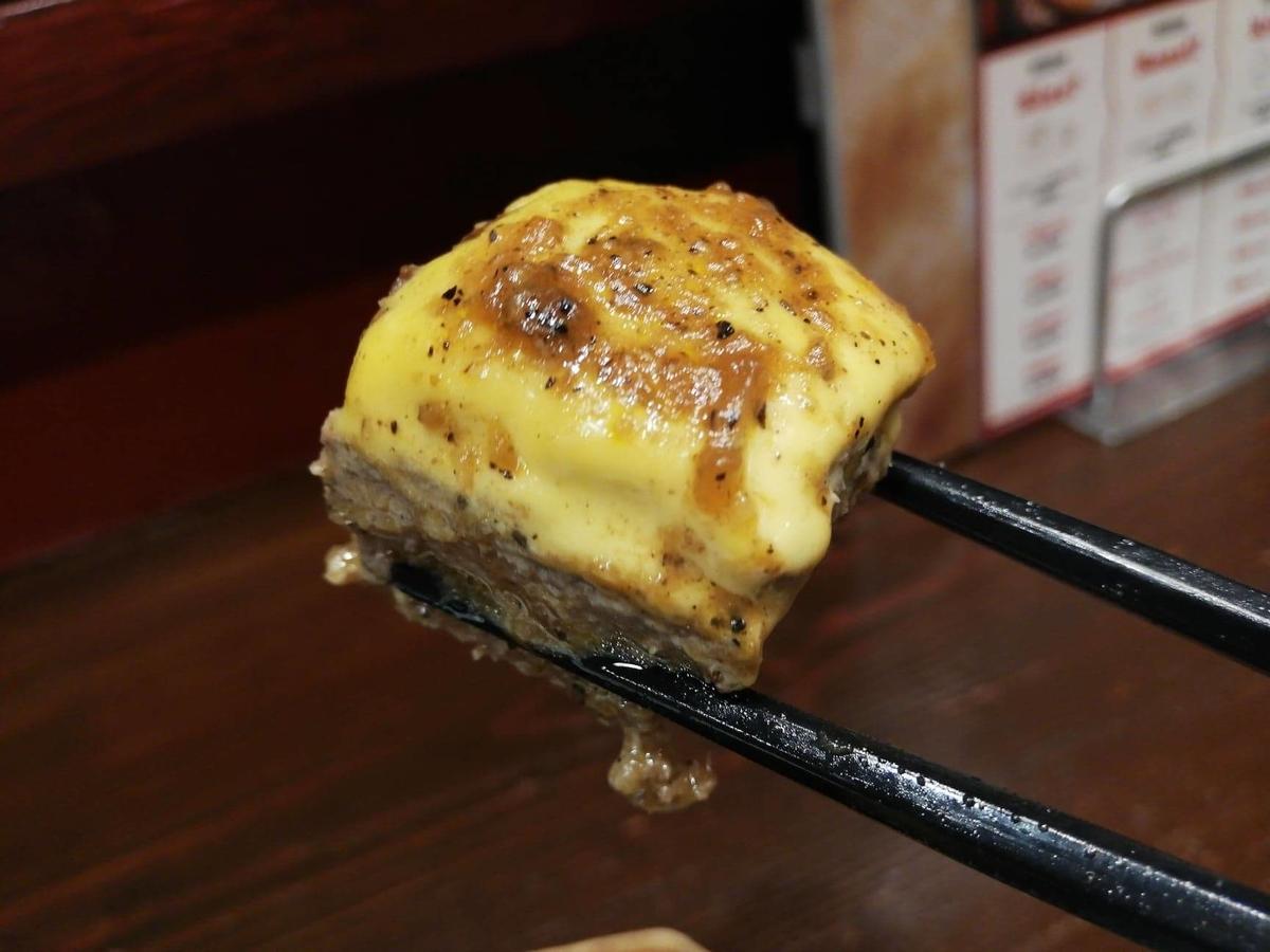 池袋『札幌牛亭』の、平日ランチタイム限定ハンバーグステーキセットのハンバーグを、チーズと一緒に箸で掴んでいる写真