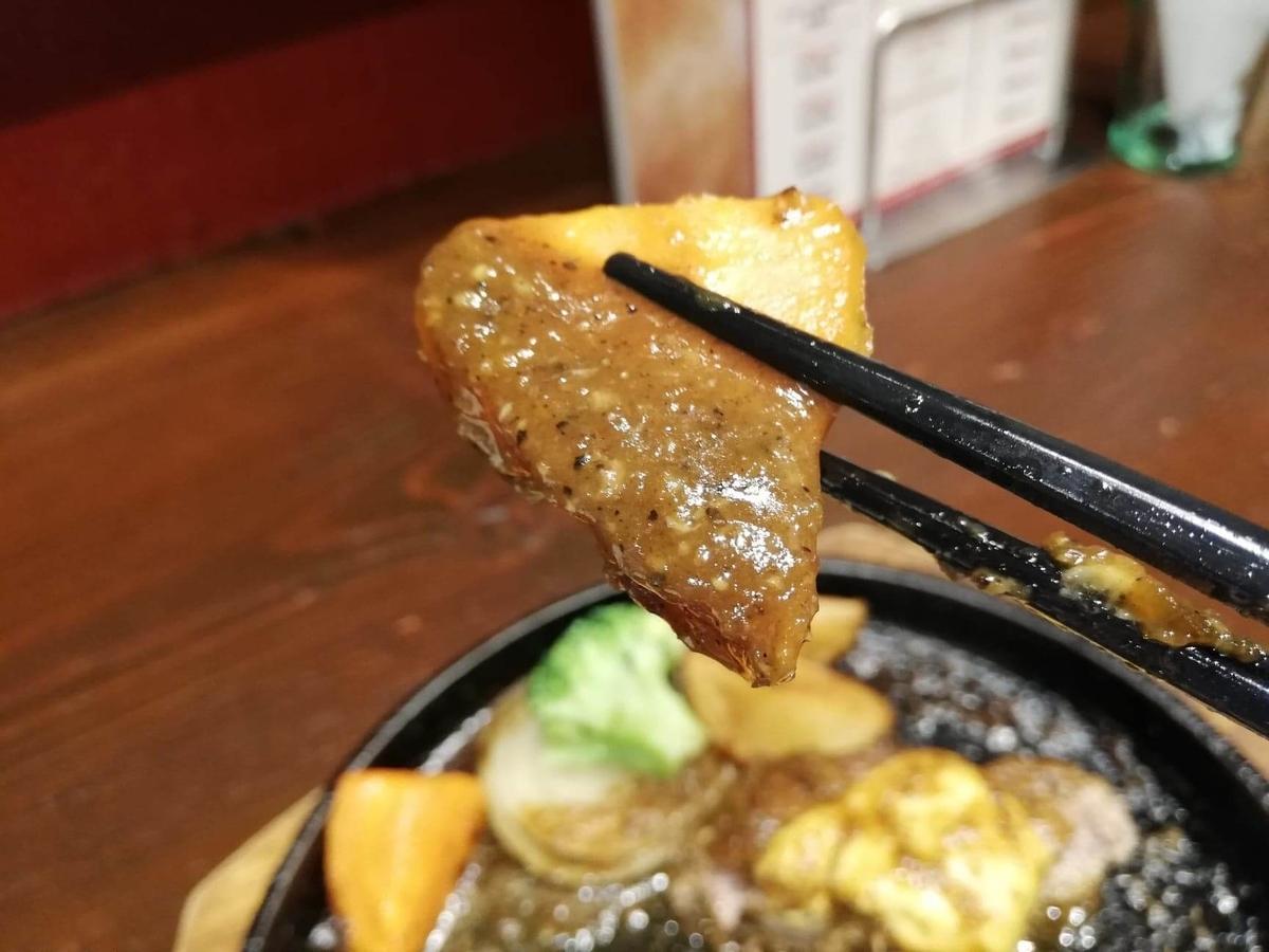 池袋『札幌牛亭』の、平日ランチタイム限定ハンバーグステーキセットのジャガイモを箸で掴んでいる写真