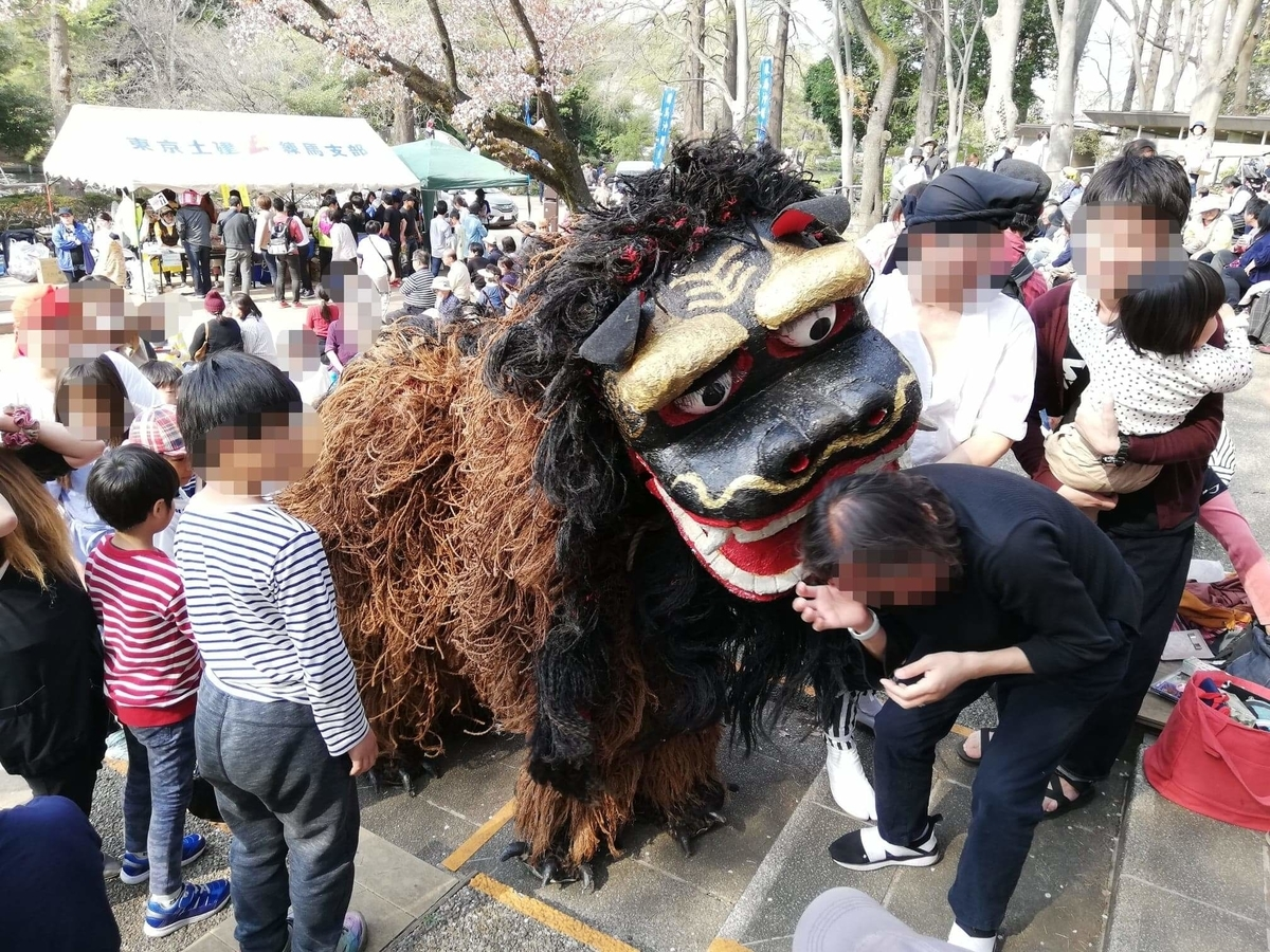 『石神井公園』のイベントスペースにいる獅子舞に、観客が噛まれている写真