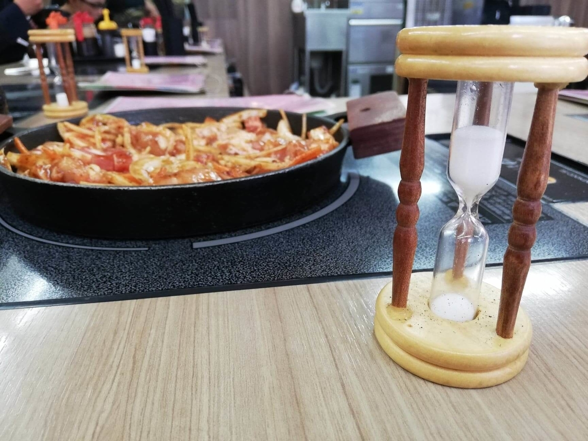 江古田『ふくふく食堂』のBBQ定食を、砂時計で測りながら焼いている写真