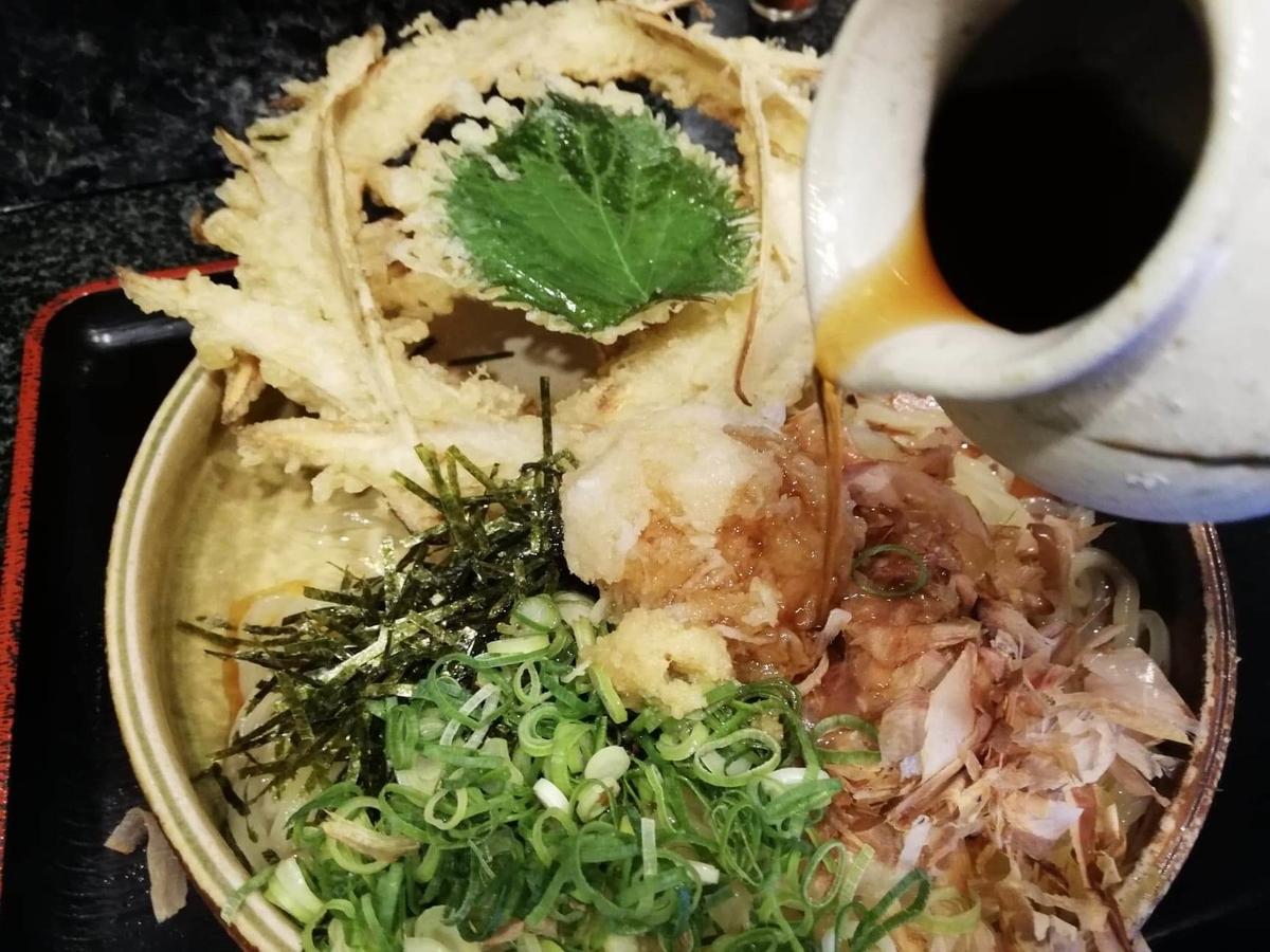 高田馬場『大地のうどん』のごぼうおろしぶっかけにタレを入れている写真