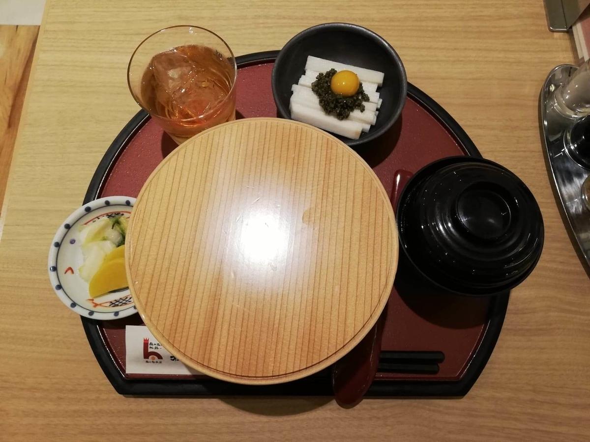 秋田駅『秋田比内地鶏や』の、比内地鶏の究極親子丼に蓋を被せた写真