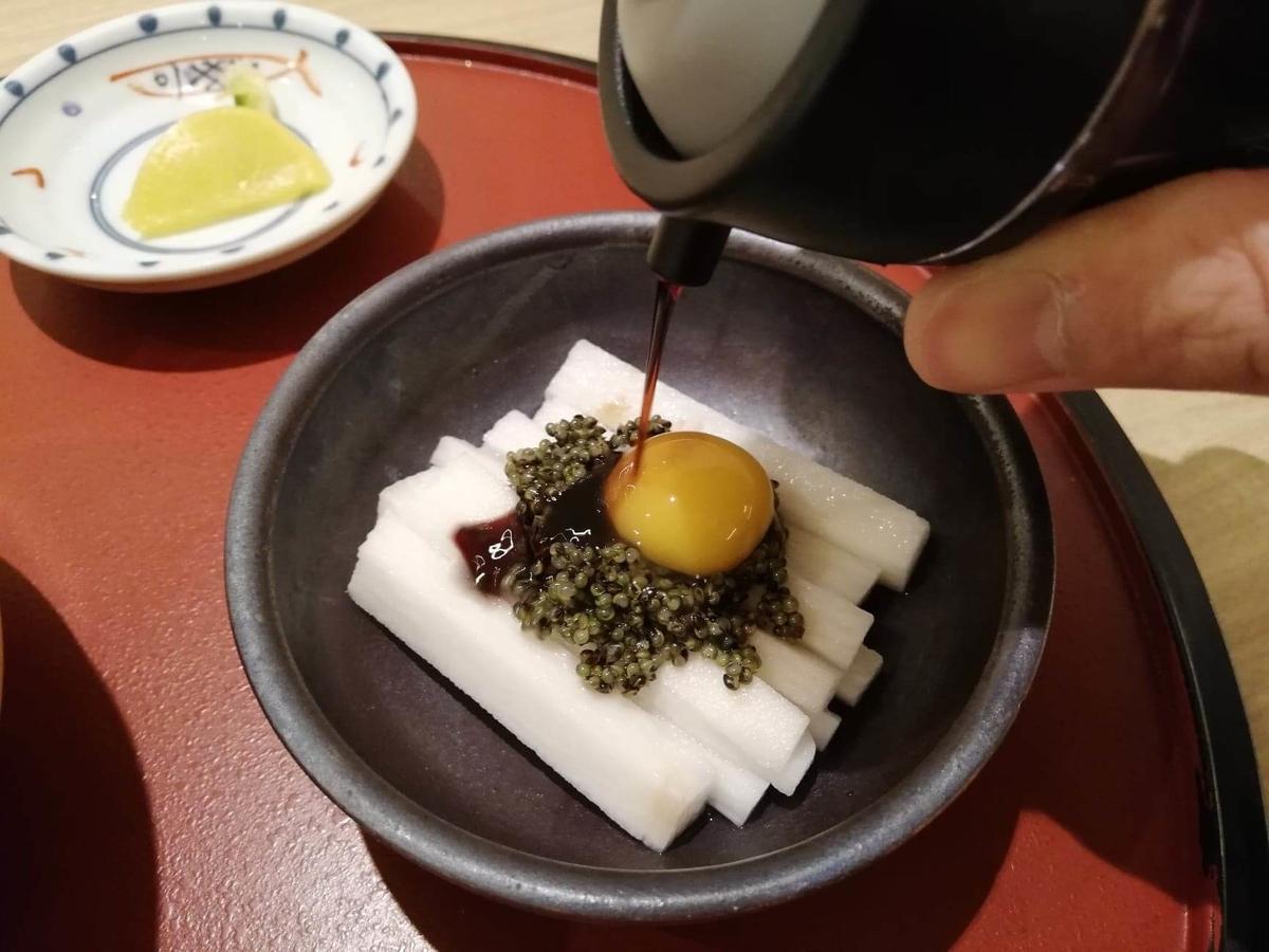 秋田駅『秋田比内地鶏や』の、長芋とんぶりに醤油をかけている写真