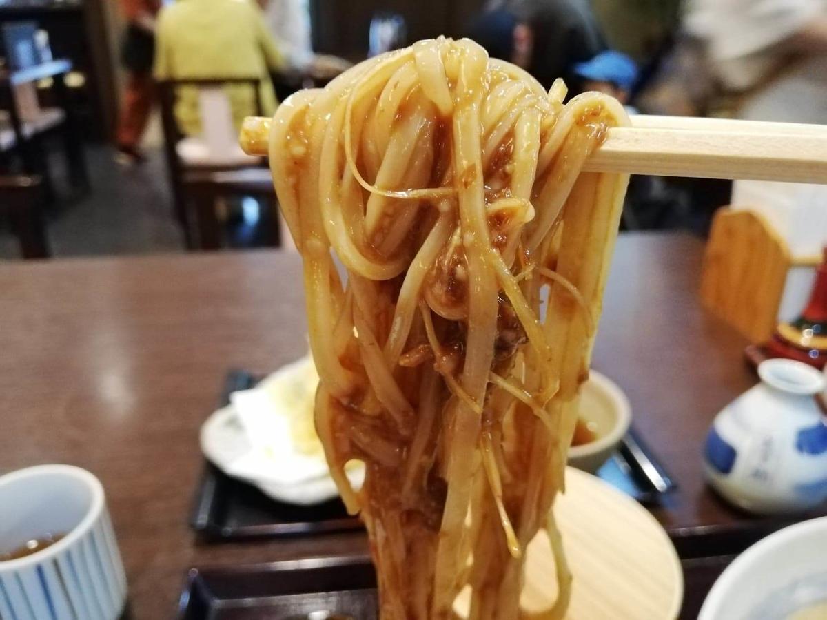 稲庭うどん『佐藤養助』秋田店の、肉味噌をつけたうどんを箸で掴んでいる写真