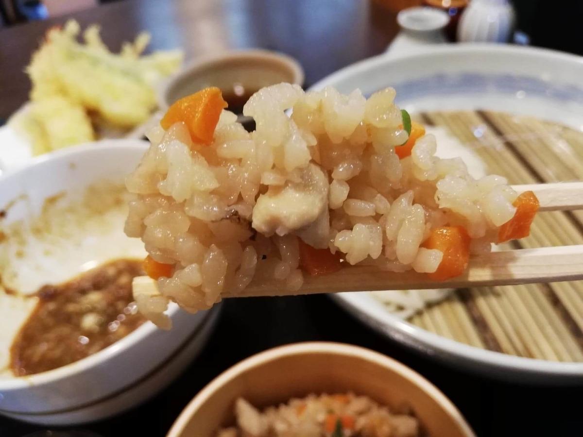 稲庭うどん『佐藤養助』秋田店の比内地鶏ご飯を箸で掴んでいる写真