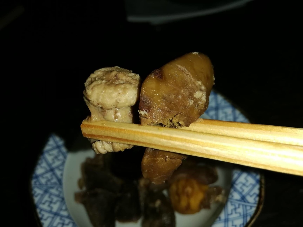 『秋田きりたんぽ屋大町分店』の比内地鶏とりモツ煮を、箸で持ち上げた写真