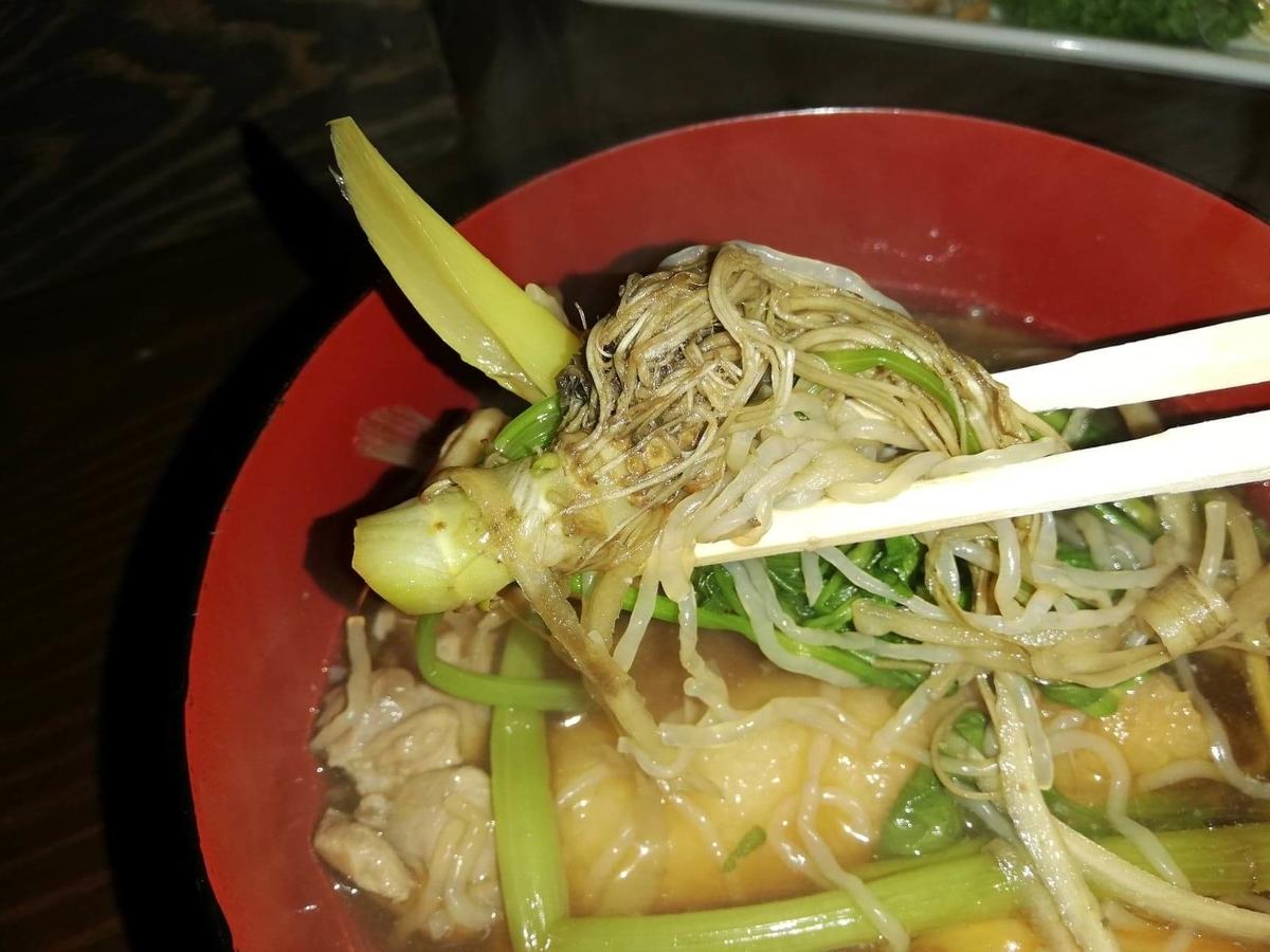 『秋田きりたんぽ屋大町分店』のきりたんぽ鍋のセリの根っこを、箸で掴んでいる写真