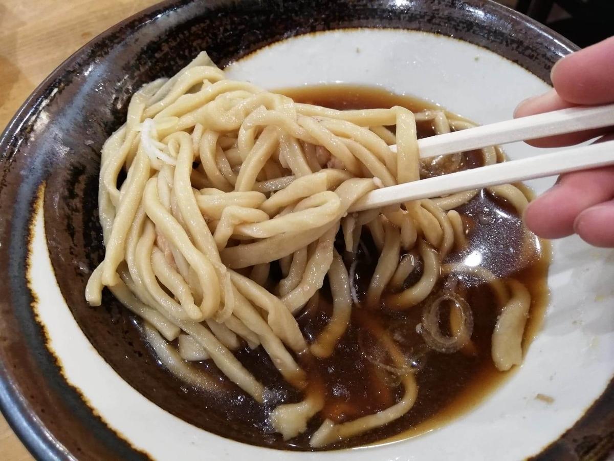 『浅草角萬』の冷やし肉南蛮の麺を、箸で持ち上げている写真