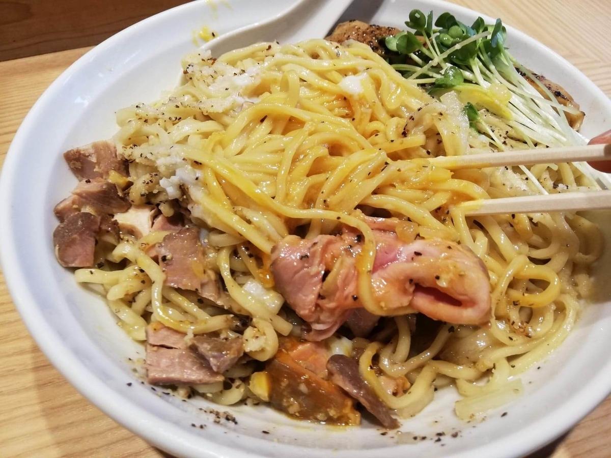 秋津(新秋津)『麺場二寅』の鶏ボナーラを混ぜている写真