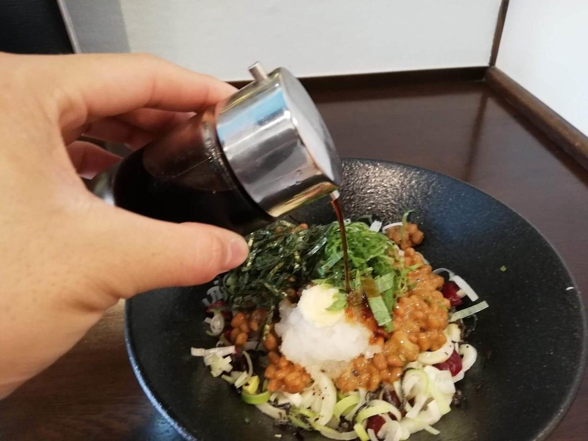 川越『創作うどん専門店くらうど』の、3種のしその納豆おろしうどんに醤油をかけている写真