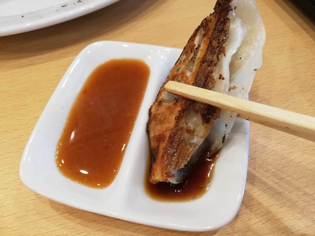 久米川『東京餃子食堂』の餃子をタレにつけている写真