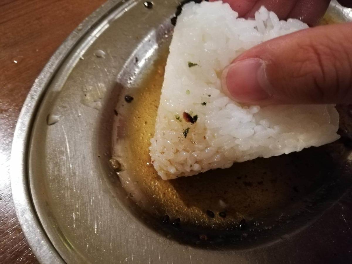 香川県高松市『骨付鳥一鶴』のおにぎりを油につけている写真