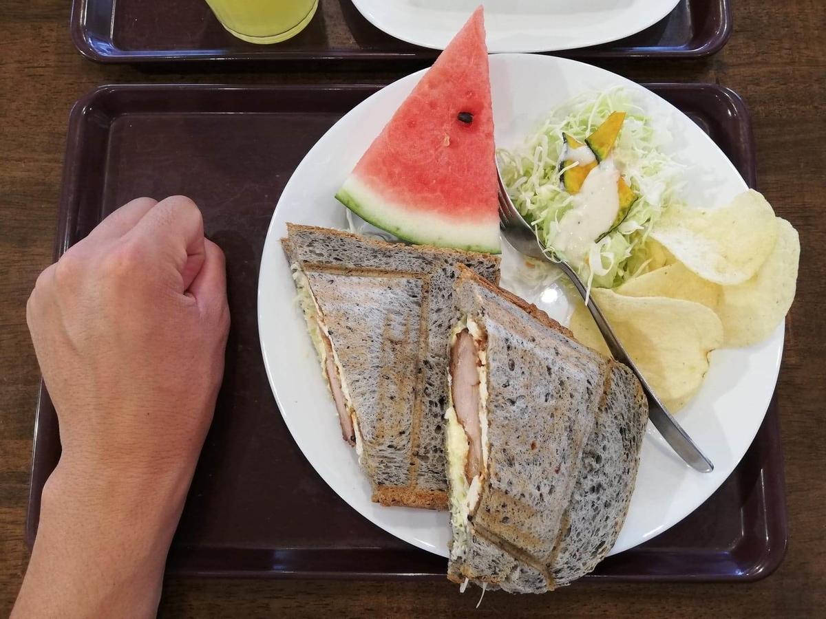 香川県高松市『三びきの子ぶた』の、テリヤキチキンチーズサンドウィッチと拳のサイズ比較写真