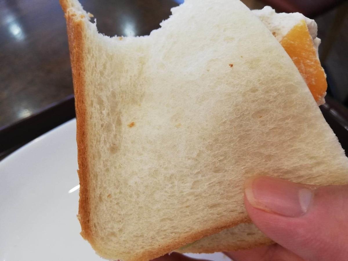 香川県高松市『三びきの子ぶた』の、フルーツサンドウィッチを持ち上げている写真