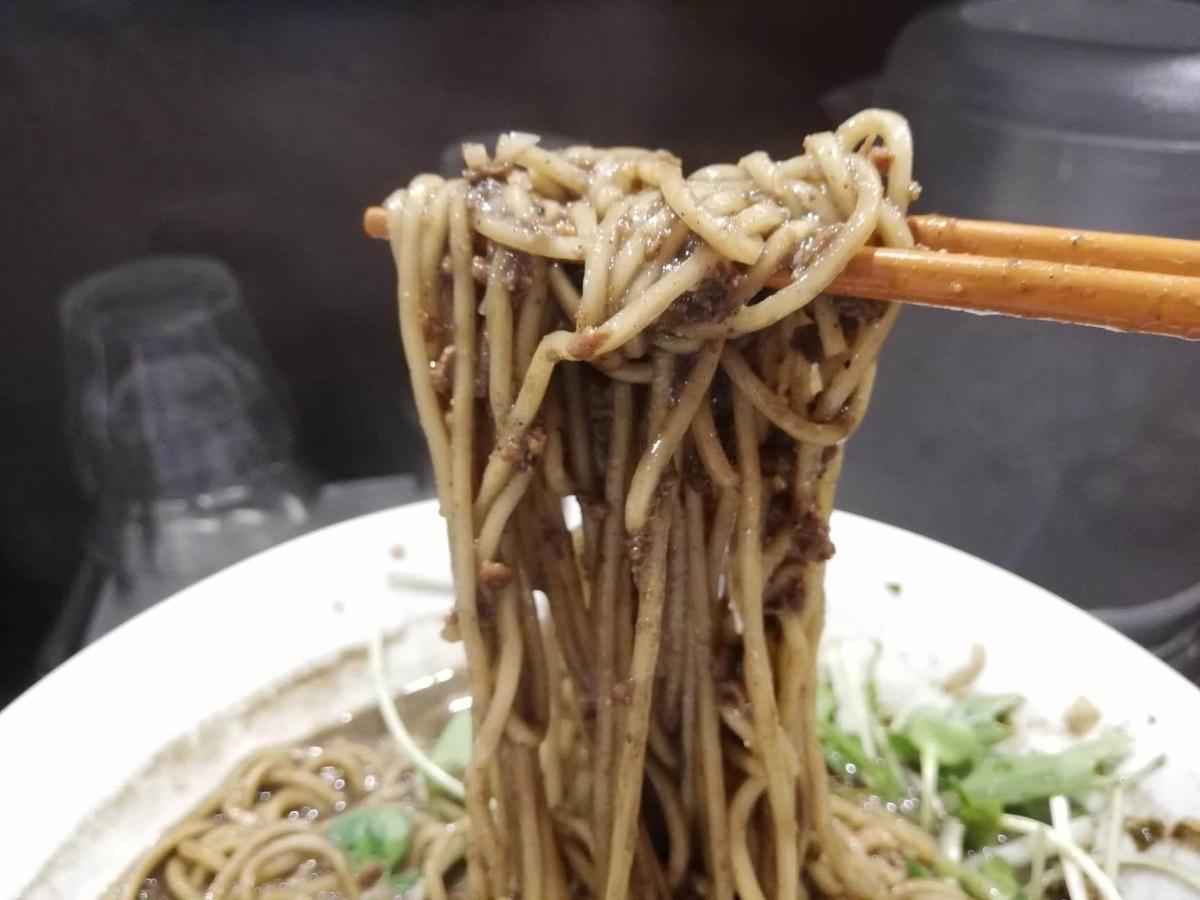 北浦和『四川担々麺(担担麺)阿吽』の黒胡麻担担麺を箸で掴んでいる写真