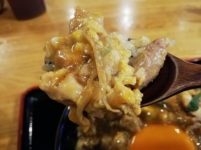 池袋『軍鶏一』の親子丼をスプーンですくっている写真