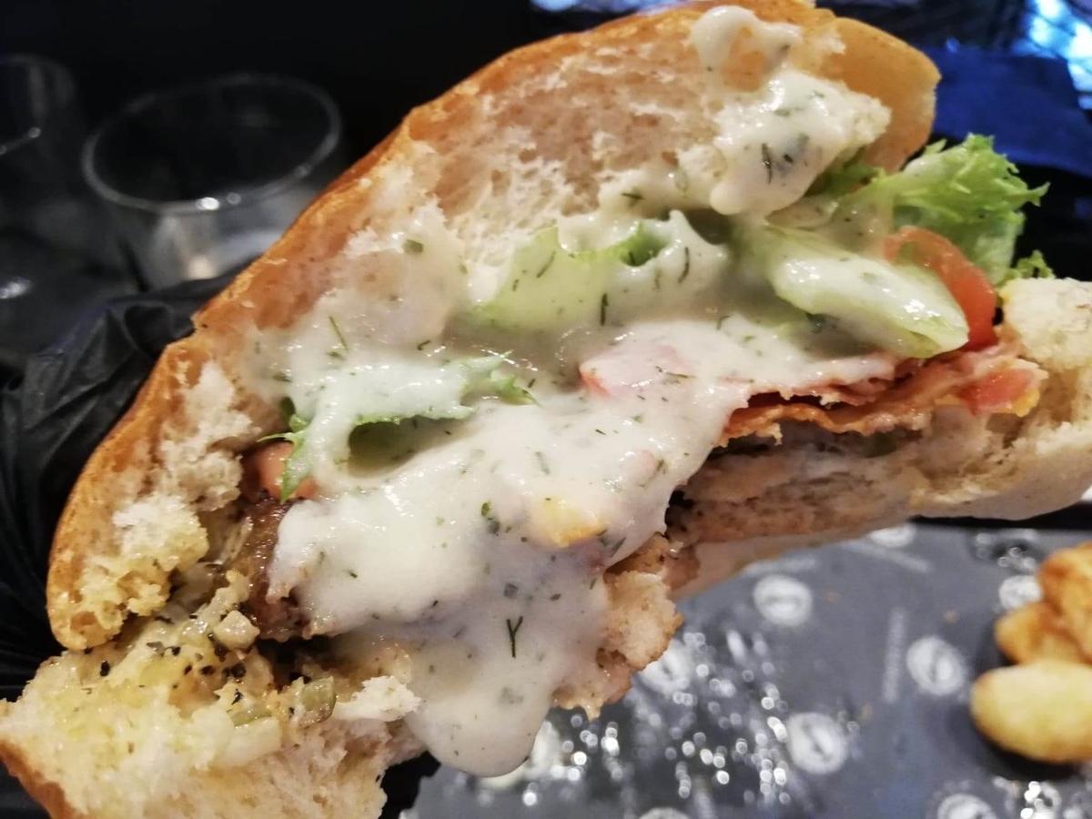 表参道『いしがまや GOKU BURGER(ゴクバーガー)』のBLTチーズバーガーにソースをかけた写真
