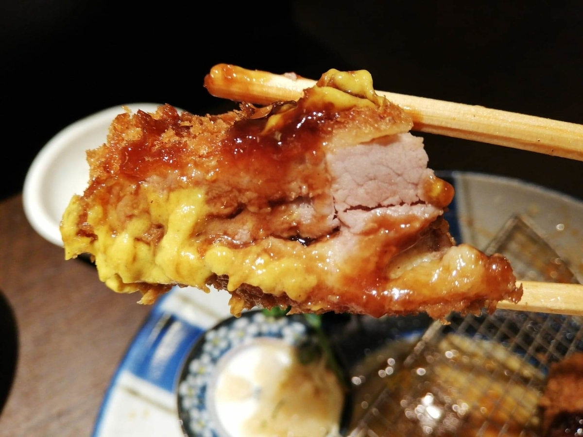 高田馬場『とん久』のとんかつを箸で掴んでいる写真