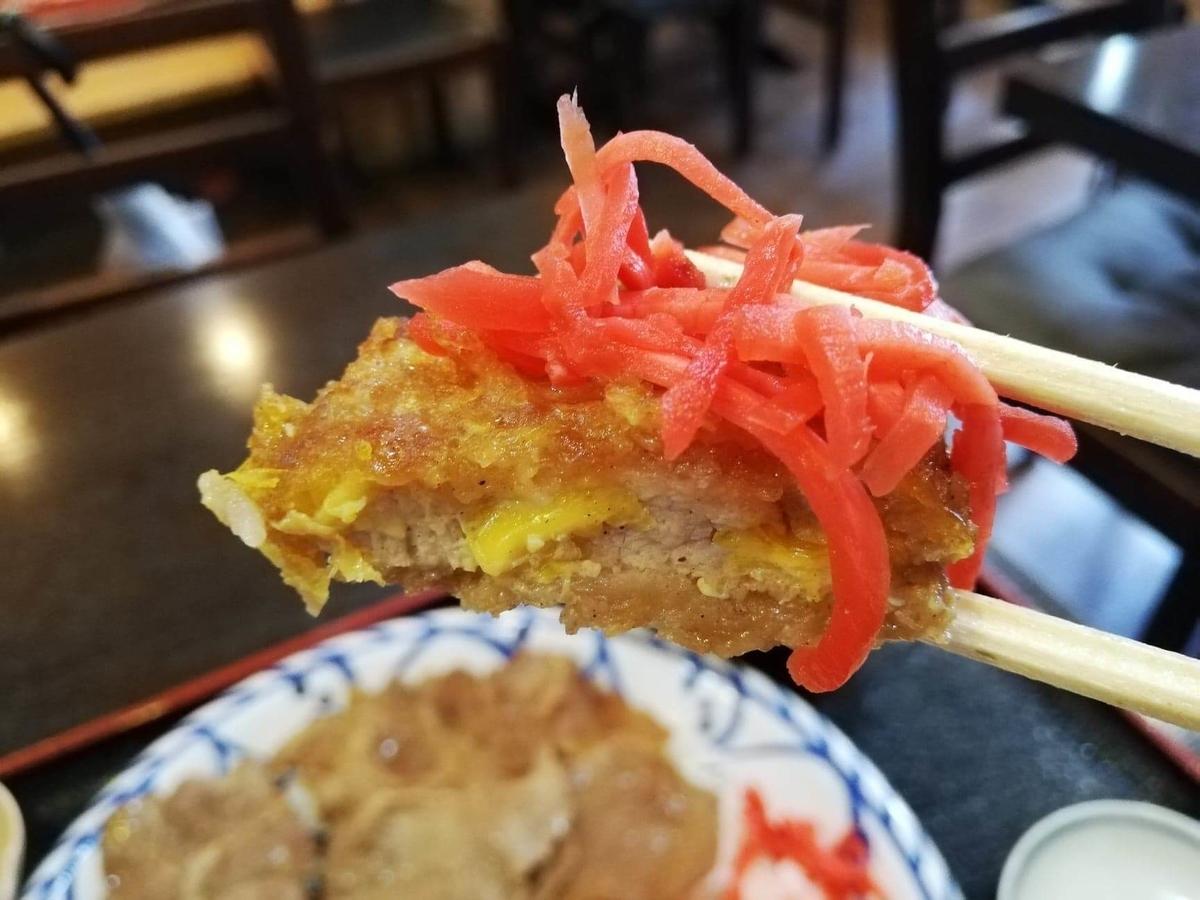 東池袋『伊東食堂』のカツに紅生姜を乗せている写真