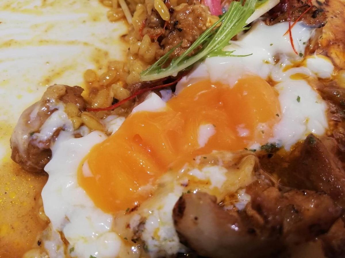 西武新宿『スパイシーCURRYハウス半月』の卵を割った写真