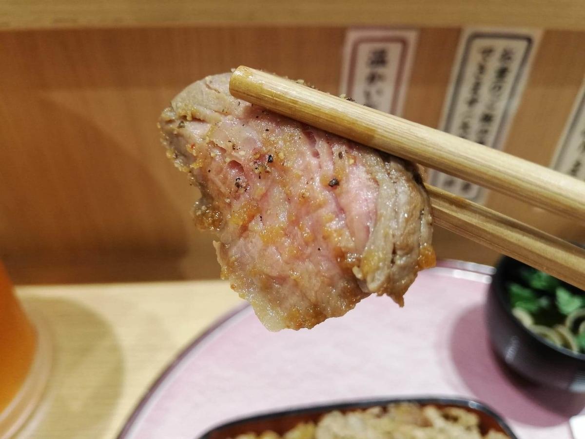 大阪『ビフテキ重・肉飯 ロマン亭』の、ビフテキを箸で掴んでいる写真