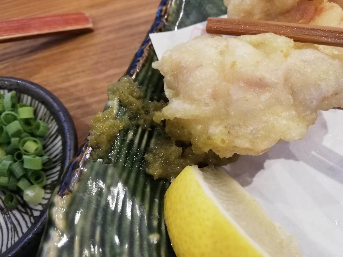 本川越『うどんとお酒土麦』の、鶏天盛に柚子胡椒をつけている写真