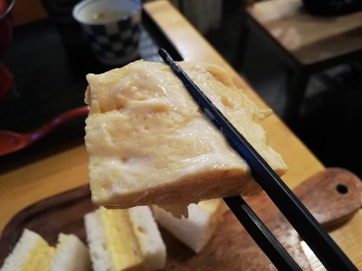 本川越『小江戸オハナ』の、貴婦人の卵サンドの卵を箸で掴んでいる写真