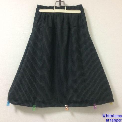 壁にかかった濃グレー(裾にクリップつき)のスカートの画像