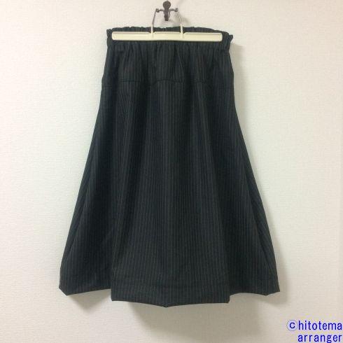 壁にかかった濃グレーのスカートの画像