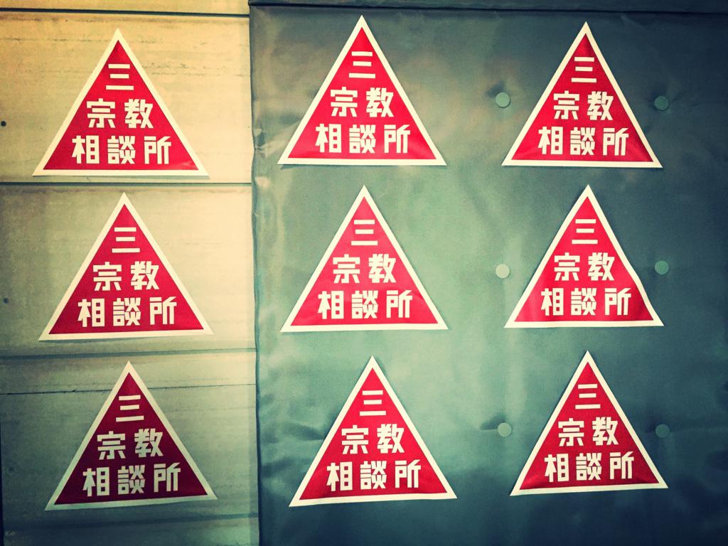 壁に貼られた三宗教相談所のステッカー