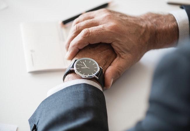 腕時計で時間を確認するサラリーマン