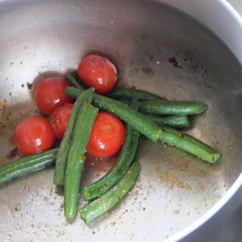 プチトマトとインゲンを炒めて味付けする